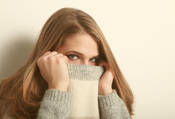 Mulher medrosa esconde a cara por baixo da camisola